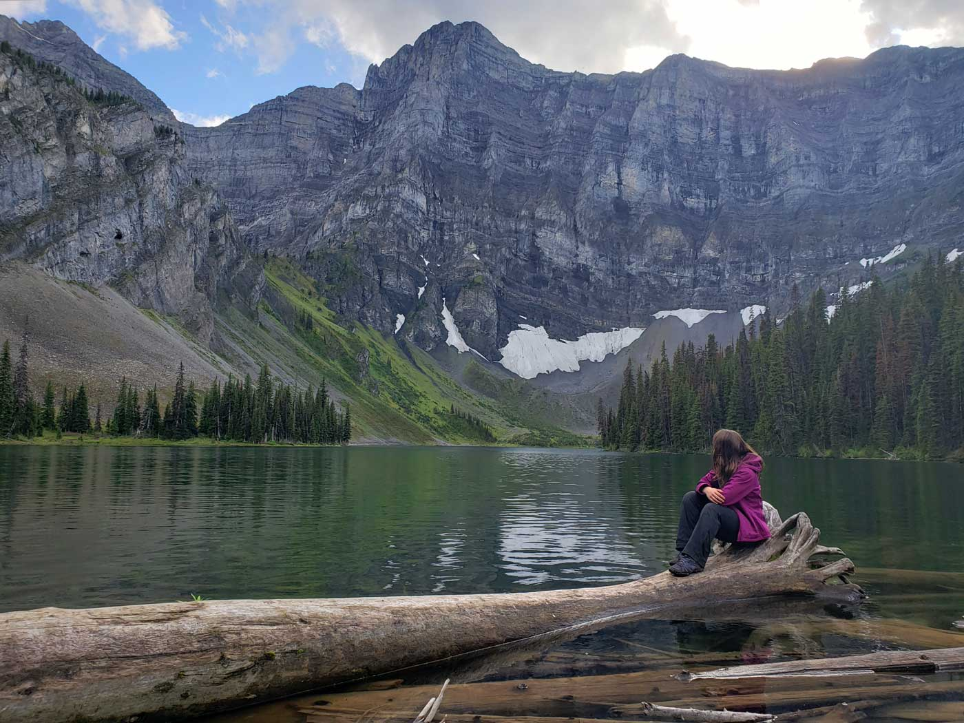 Jolene Rempel sitting on log in Rawson Lake in Kananaskis Country, Alberta, Canada.